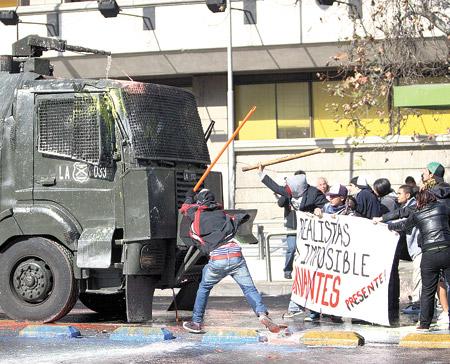 Estudiantes chilenos cargan contra un camión hidrante en una calle de Santiago, en la protesta del jueves pasado.